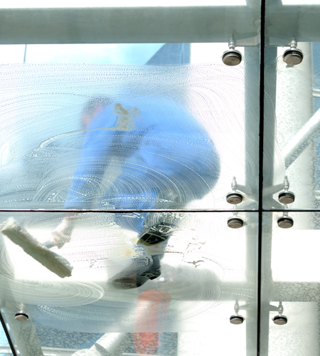 Man Cleaning a Glass Floor in Houston, TX
